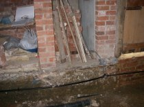 Installing a ring main before the floor was laid.