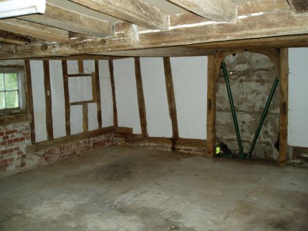 The living room before work started, showing the blocked doorway and frame and the concrete floor