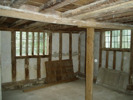 The kitchen before work began showing two of the old shutters and the rotten central beam